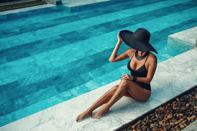 Portrait of fashion stylish pretty woman posing in the swimming pool wearing elegant black hat