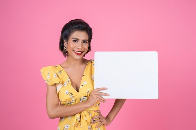 Portrait of fashion woman displaying white banner
