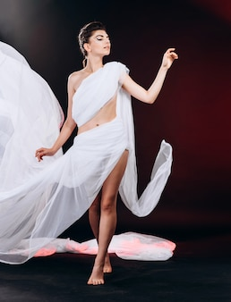 Portrait of fashion woman standing wrapped in a white cloth and dancing