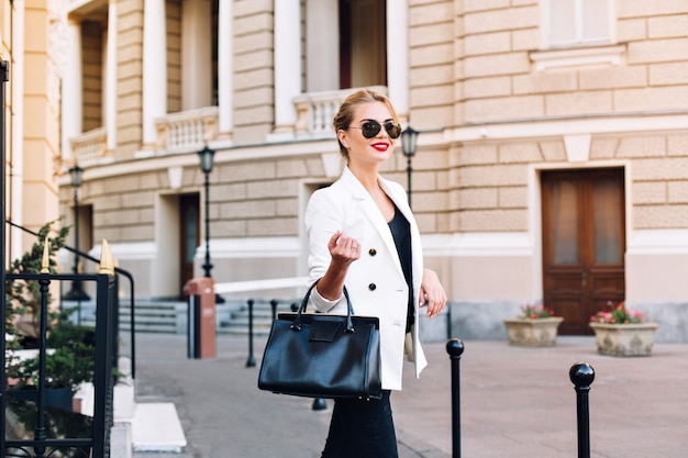 Portrait fashion woman in sunglasses walking on street. she is smiling to side.