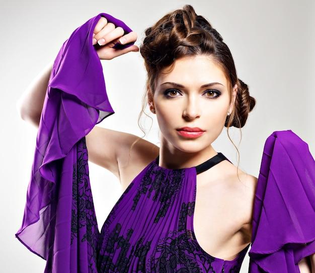 Il ritratto della donna di modo in vestito viola con l'acconciatura alla moda pone allo studio