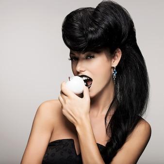 Ritratto di donna moda con acconciatura moderna morde la mela bianca