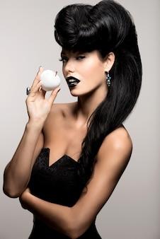 Ritratto di donna moda con acconciatura moderna e labbra in colore nero con mela bianca