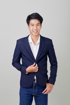 Portrait of fashionable asian businessman on bright gray