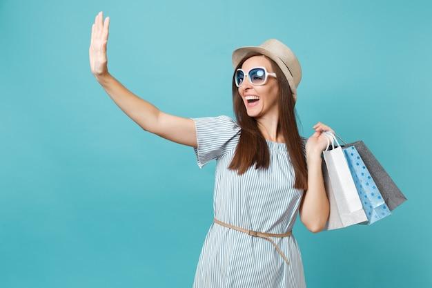 夏のドレス、麦わら帽子、青いパステル背景で隔離の買い物後の購入でパッケージバッグを保持しているサングラスの肖像画のファッショナブルな魅力的な幸せな女性。広告用のスペースをコピーします。