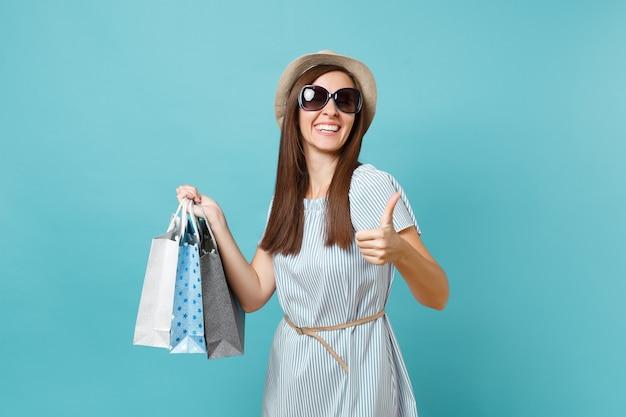 Портрет модной привлекательной счастливой женщины в летнем платье, соломенной шляпе, солнцезащитных очках, держащих пакеты с покупками после покупок, изолированных на синем пастельном фоне. скопируйте место для рекламы.