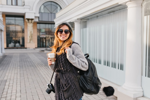 Portrait fashionable attractive woman walking with coffee to go in city centre. young smiling stylish woman in modern sunglasses, winter sweater, knitted hat travelling with bag, camera.