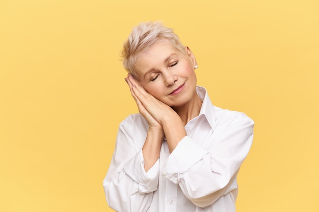 Ritratto di donna bionda alla moda in pensione in posa isolato piegando la testa, tenendo i palmi sotto la guancia e tenendo gli occhi chiusi, dormendo, sonnecchiando, sorridendo con piacere, avendo un buon sogno