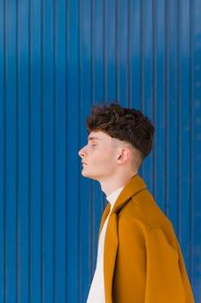 Portrait of fashionable boy against blue wall