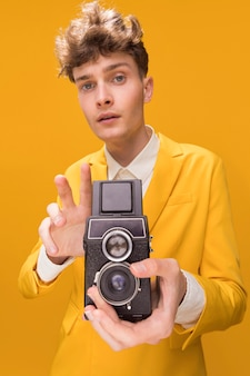 Portrait of fashionable boy filming with a camcorder