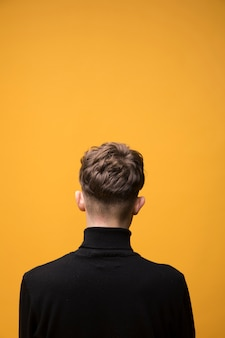 Portrait of fashionable boy from behind