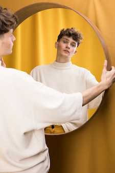 Portrait of fashionable boy in front of mirror