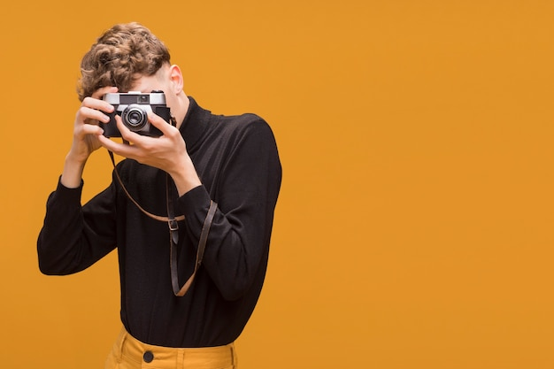 Portrait of fashionable boy taking a photo