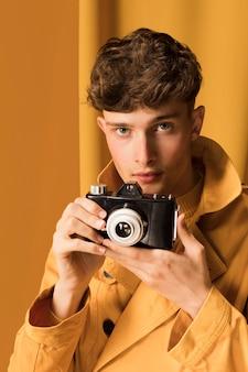 Portrait of fashionable boy taking a photo