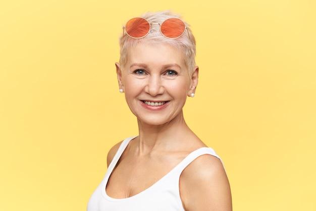 Ritratto del pensionato femminile caucasico alla moda che cammina sulla giornata calda e soleggiata indossando occhiali da sole rosa rotondi sulla sua testa, guardando la fotocamera con un sorriso felice