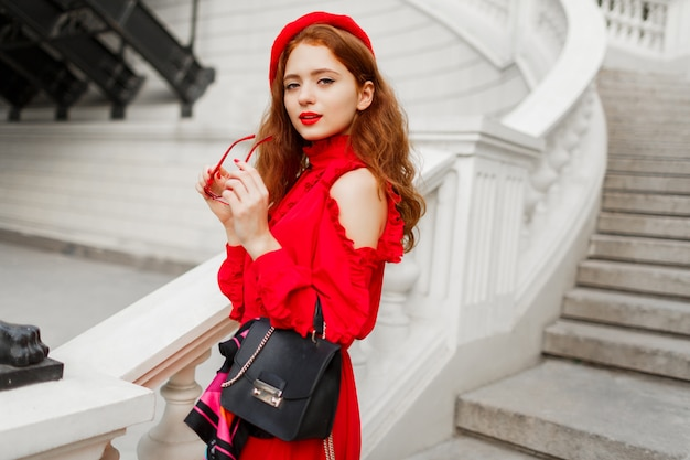 Portrait of fashionable ginger female in red beret and elegant dress posing outdoor.