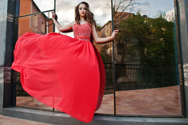 Portrait of fashionable girl at red evening dress posed background mirror window of modern building. blowing dress in the air