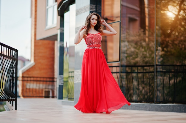 Portrait of fashionable girl at red evening dress posed background mirror window of modern building at sunset