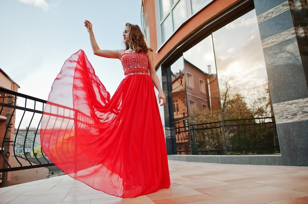 Portrait of fashionable girl at red evening dress posed background mirror window of modern building at terrace balcony. blowing dress in the air