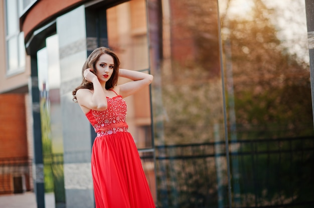 Portrait of fashionable girl at red evening dress posed background mirror window of modern building