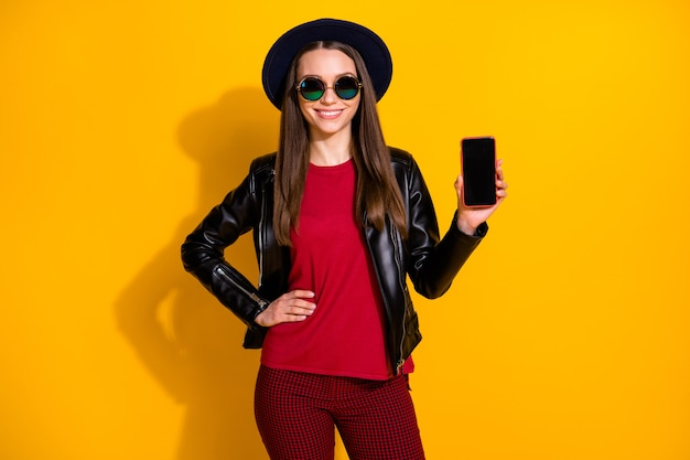 Portrait of fashionable girl showing phone device touchscreen empty space