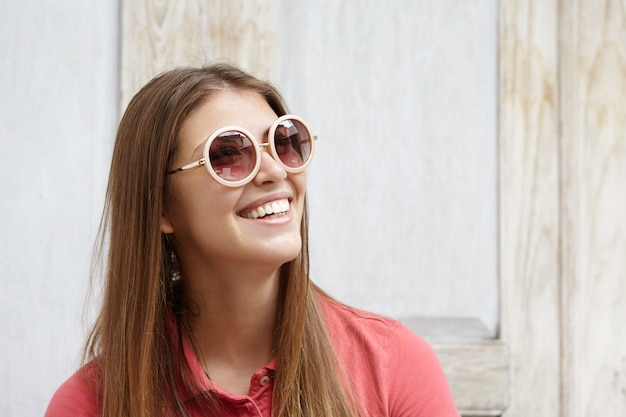 Portrait of fashionable girl wearing round sunglasses with mirror lenses and polo shirt looking up with happy smile, showing her white teeth, standing isolated against wooden wall