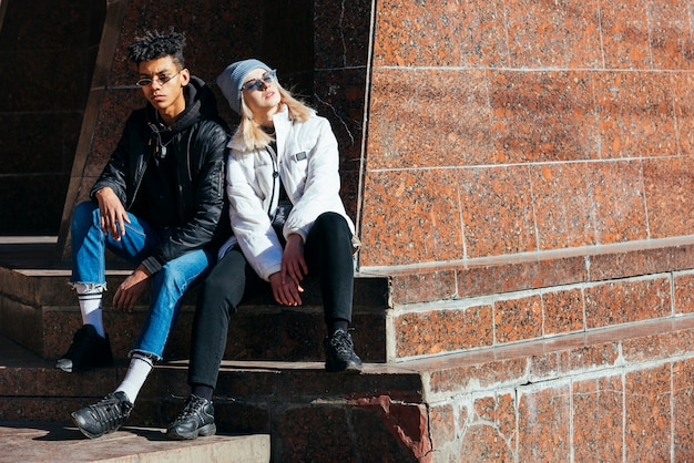 Portrait of fashionable interracial young couple sitting outdoor