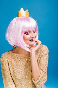 Portrait fashionable joyful young woman with cut pink hair. smiling with closed eyes, makeup with pink tinsels, happiness, party, celebrating new year, birthday, carnival.