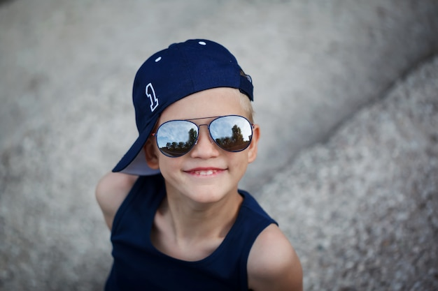 Portrait of fashionable little boy in sunglasses and cap. childhood.  summertime.