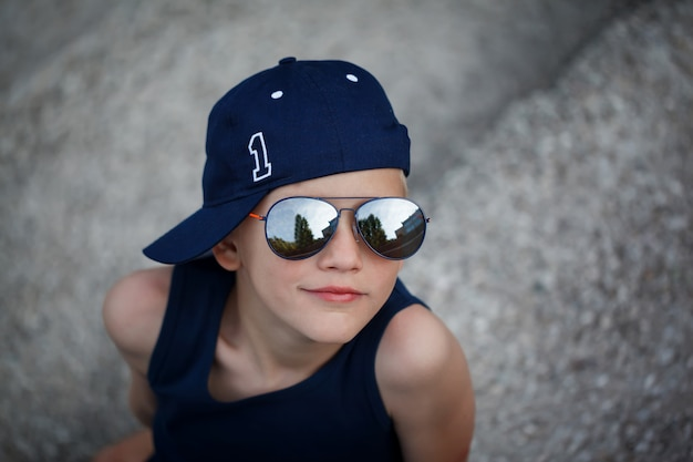 Portrait of fashionable little boy in sunglasses and cap. childhood.  summertime