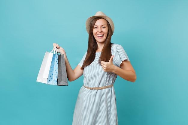 Портрет модной улыбающейся красивой кавказской женщины в летнем платье, соломенной шляпе, держащей пакеты с покупками после покупок, изолированных на синем пастельном фоне. скопируйте место для рекламы.