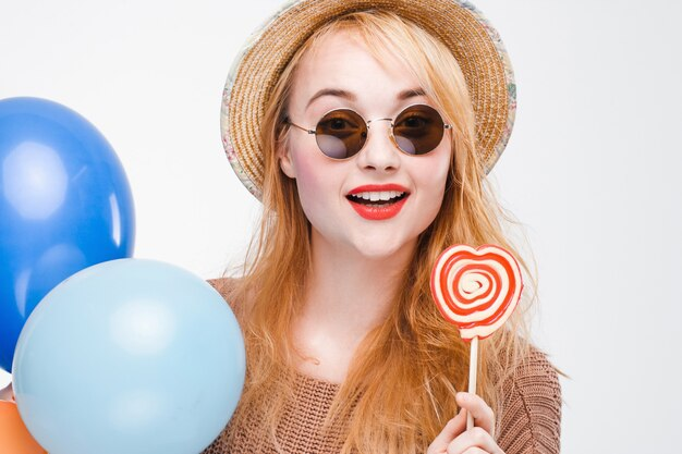 Portrait of fashionable smiling hipster girl with lollipop and balloons. happy young woman in sunglasses and straw hat having fun, close up