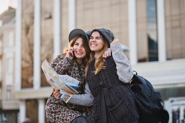 Donne sorridenti alla moda del ritratto che esprimono emozioni luminose in giornata di sole in città. buon viaggio insieme, bei momenti di gioiosi toutisti, stile, vacanza, conversazione al telefono.
