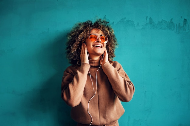 Portrait of fashionable smiling young woman with curly hair listening to the music and looking away.
