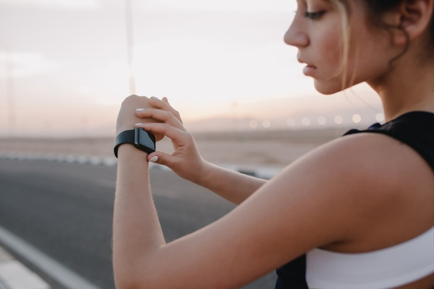 Portrait fashionable sportswoman looking at modern watch on hands of on road in sunny morning. training of attractive woman, workout, healthy lifestyle, hardworking