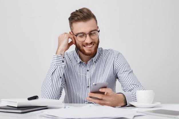 Il ritratto del responsabile maschio alla moda alla moda ascolta la musica sugli auricolari, guarda deliziosamente nello schermo del computer portatile