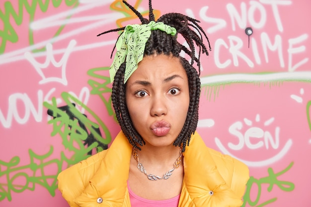 Portrait of fashionable teenage girl make grimace at camera pouts lips has combed dreadlocks belongs to youth subculture poses in urban place against colorful drawn graffiti wall