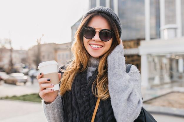 Ritratto alla moda urbana giovane donna con caffè per andare a piedi nel soleggiato centro città. incredibile donna sorridente in occhiali da sole moderni, cappello lavorato a maglia, maglione di lana divertendosi all'aperto.