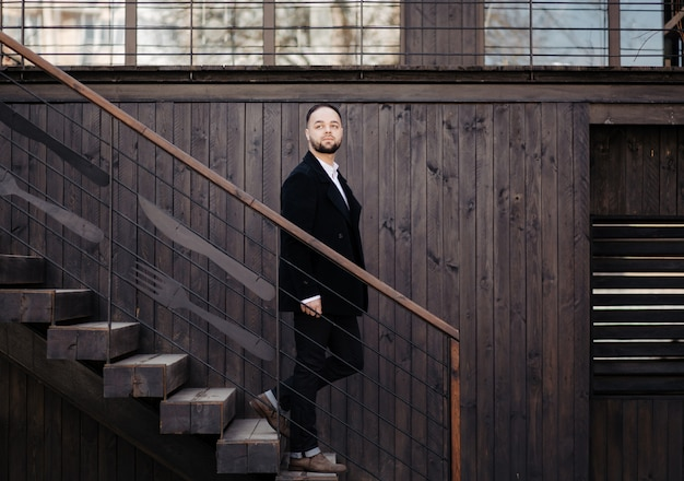 Portrait of fashionable well dressed man with beard posing outdoors