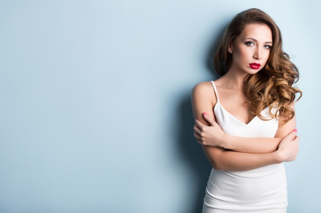 Portrait of fashionable woman over blue wall.
