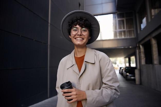 Ritratto di giovane donna alla moda riccia con taglio di capelli corto che sorride felicemente mentre sta sopra un edificio urbano nero, vestita di trincea beige, occhiali e cappello grigio largo