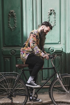 Portrait of a fashionable young man riding the bicycle