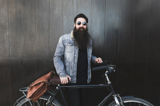 Portrait of a fashionable young man wearing sunglasses standing in front of black wooden wall with the bicycle