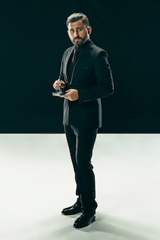 Portrait of a fashionable young man with stylish haircut wearing trendy suit posing over black.