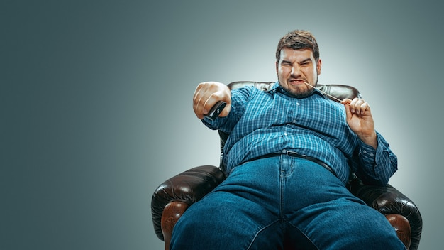 Portrait of fat caucasian man wearing jeanse and whirt sitting in a brown armchair isolated