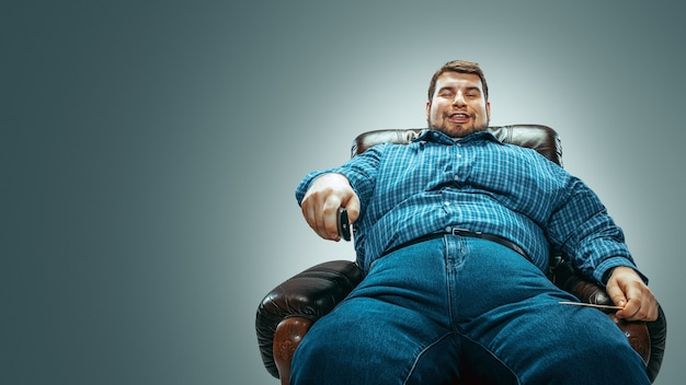 Portrait of fat caucasian man wearing jeanse and whirt sitting in a brown armchair