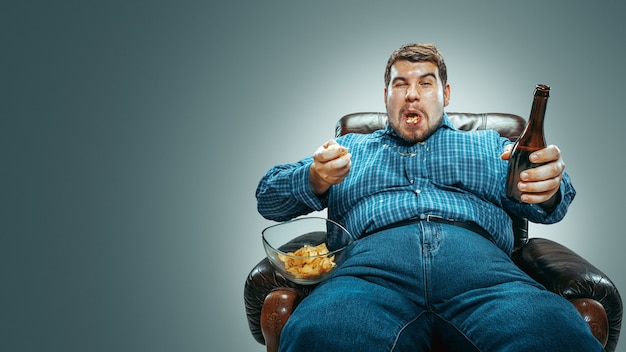 Portrait of fat caucasian man wearing jeanse and whirt sitting in a brown armchairbackground