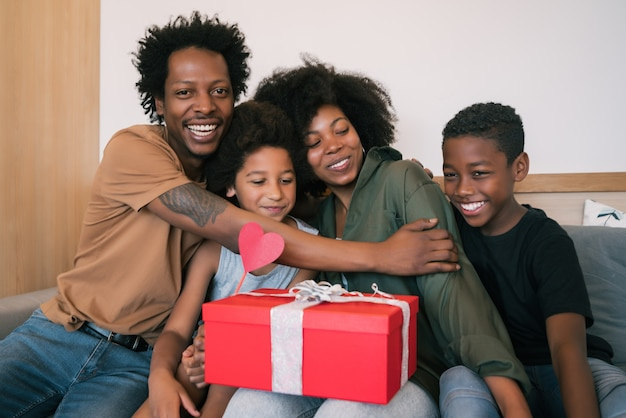 Portrait of father and children congratulate mother on mother's day and give her gifts at home