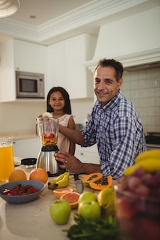 Portrait of father and daughter preparing smoothie in kitchen