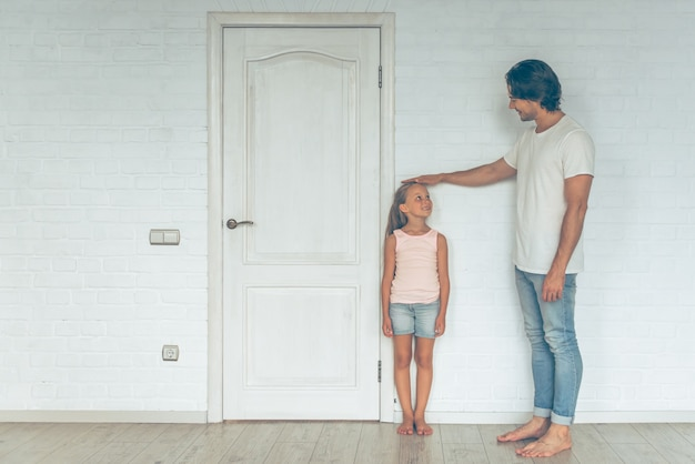 Portrait of father measuring height of his cute daughter.